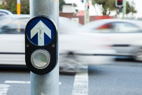 Traffic pedestrian crossing light button with cars zooming past
