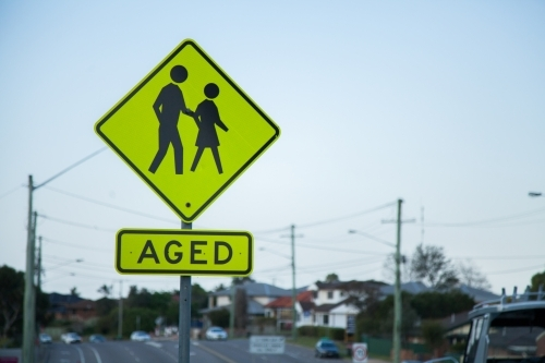 AGED yellow reflective sign beside busy road in Newcastle