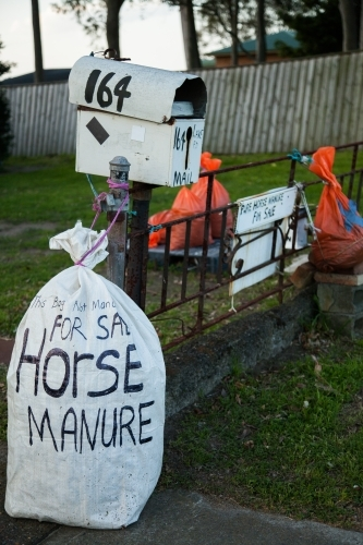 Orange bags of horse manure for sale on someones front lawn