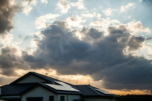 Solar panels on house roof with sunset and clouds behind