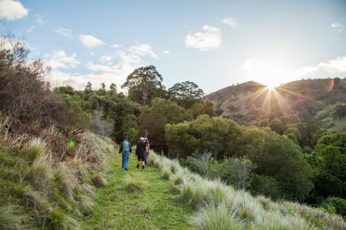 Sunrise in the mountains and people hiking along a track