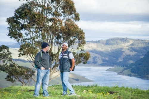 Two bushwalkers standing on a hill overlooking Lake St Clair