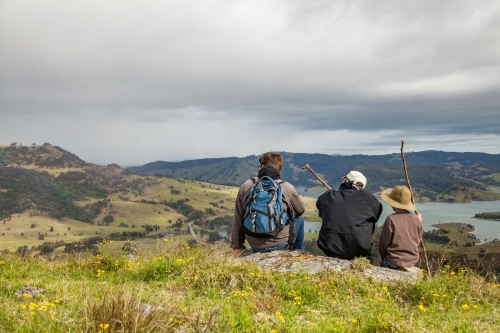 Three boys sitting on a rock in the hills watching rain come in