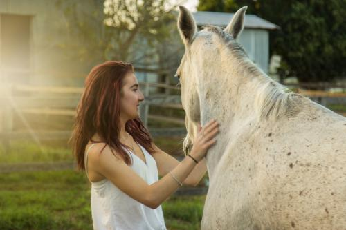 Teenager standing next to her horse