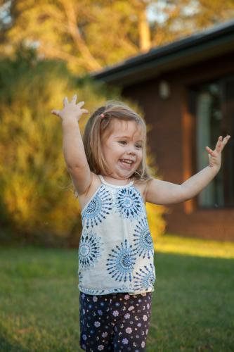 Happy little girl throwing grass into the air