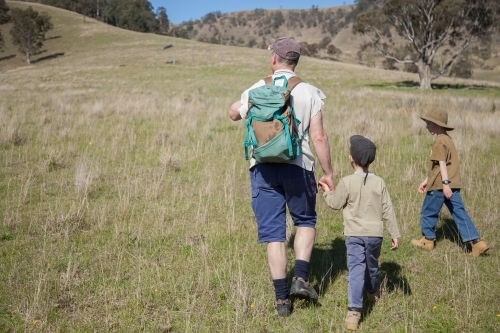 Dad and two young sons bushwalking through a paddock