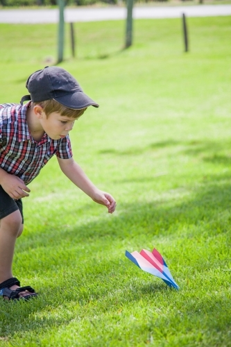 Young boy flying paper plane outside on grass