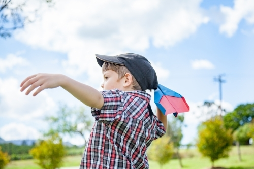 Young boy flying a paper plane outside