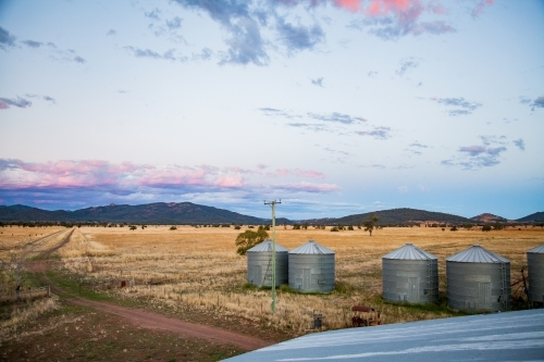 Grain silos on a farm at dusk with pink clouds