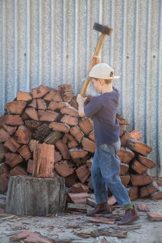 Young boy splitting wood for the fire with a axe
