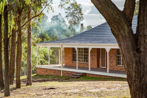 Home among gum trees with veranda and smoke drifting from chimney