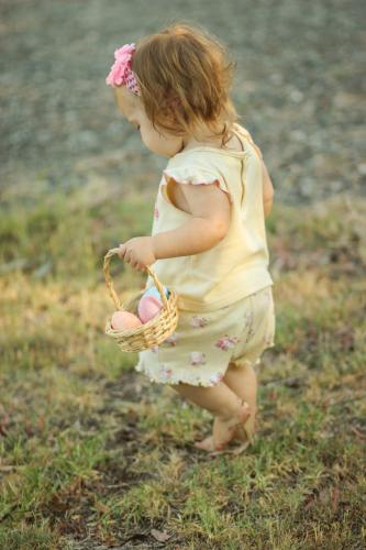Toddler carrying a basket of easter eggs