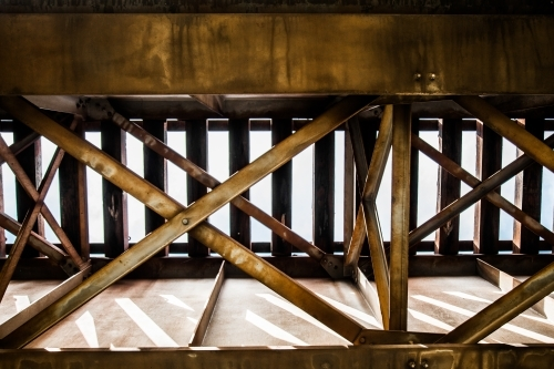 Looking up at metal structure underneath a train bridge