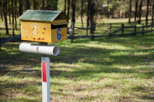 Yellow and green number six rural mailbox