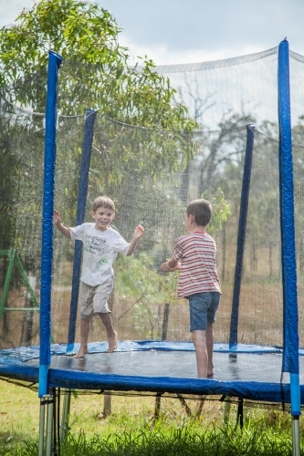 Two boys jumping on the trampoline in the rain