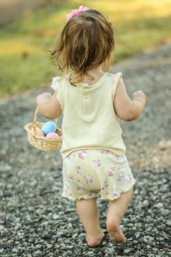 Walking baby carrying a basket of Easter eggs