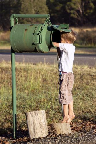 Young boy reaching to check for mail in the milk can mailbox