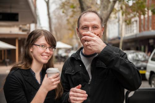 Father and daughter having a coffee together in the street