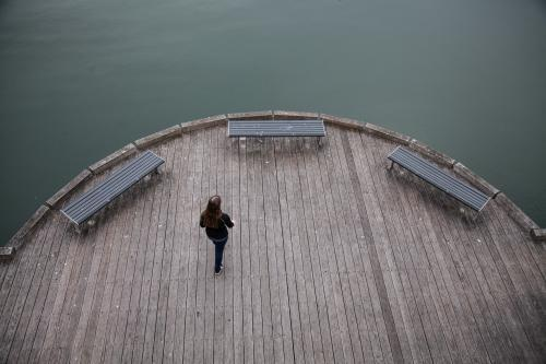 Overhead shot of teen girl walking over wooden Newcastle ferry wharf