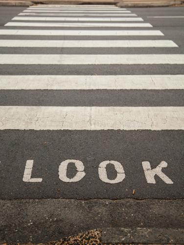 Look sign before black and white pedestrian crossing on road