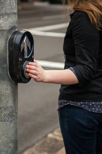 Teen girl pedestrian pressing the button at traffic lights street crossing