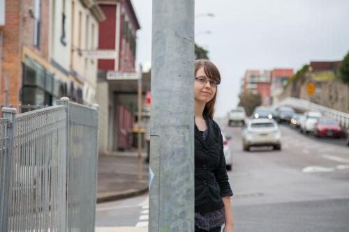 Teen girl with glasses standing beside a metal pole on the street