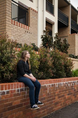 Teen girl sitting on brick wall of city house gardens