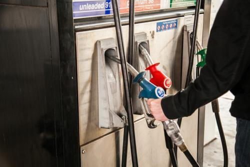 Man lifting petrol pump nozzle to fill up car with fuel
