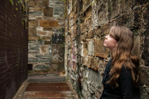 Young teen girl leaning on alleyway wall looking up