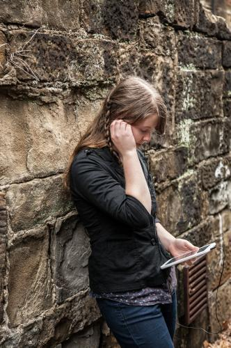 Young teen girl leaning on stone alley wall listening to music