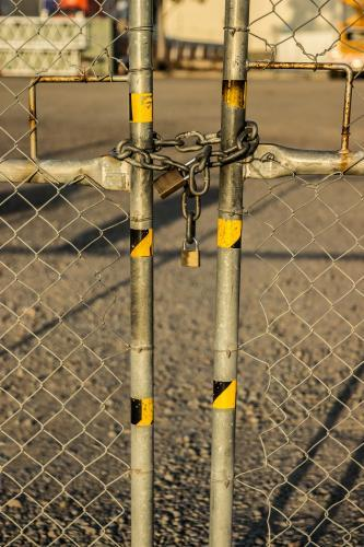Chain and padlocks holding a gate in an industrial state closed