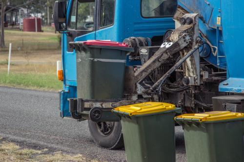 Rubbish from bins being collected by garbage truck
