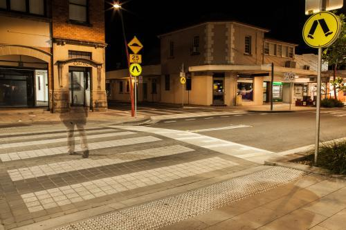 Long exposure of young woman walking over a pedestrian crossing