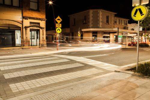 Long exposure of pedestrian crossing with car light trails at night