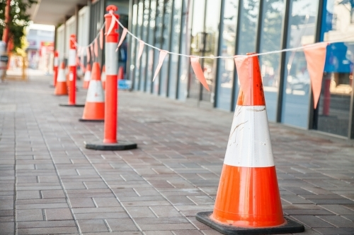 Orange traffic cones keeping pedestrians away from worksite on footpath