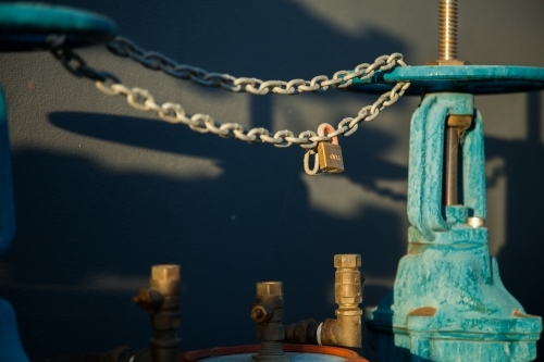 Lock on wheels and chains on a blue water hydrant