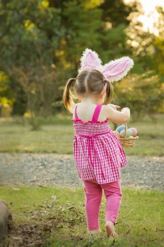 Young girl with bunny ears carrying a basket of Easter eggs