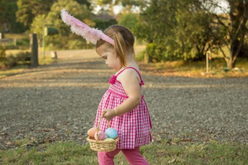 Little girl carrying a basket of Easter eggs