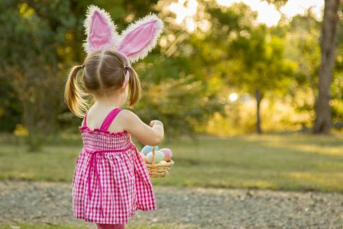 Little girl with bunny ears carrying a basket of Easter eggs