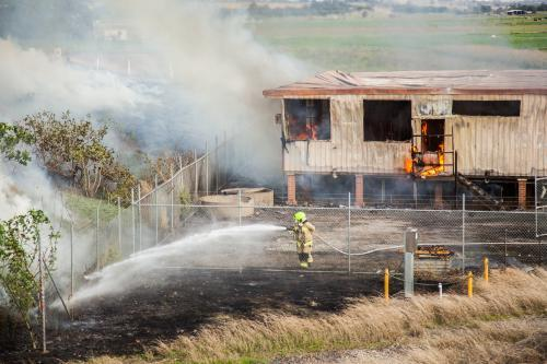 Firefighters putting out the flames of a burning shed and grass