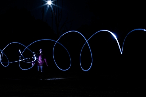 Light trails from a torch and the moon with person standing in darkness