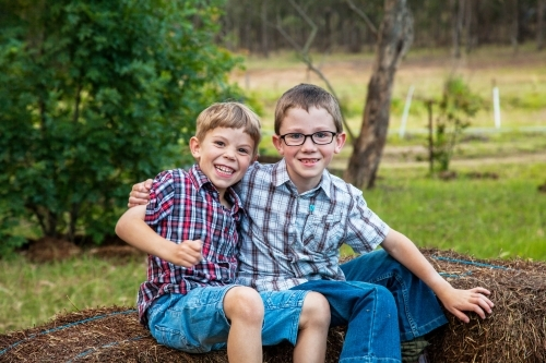 Two brothers sitting together on hay bales grinning