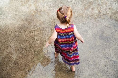 Little girl running around in puddles on concrete after rain