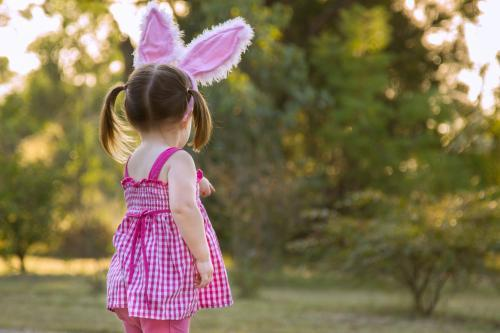 Little girl with Easter bunny ears pointing away