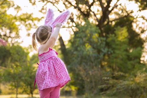 Young child wearing Easter bunny ears outdoors