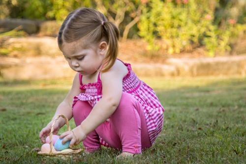 Young child placing Easter eggs in a basket on the lawn