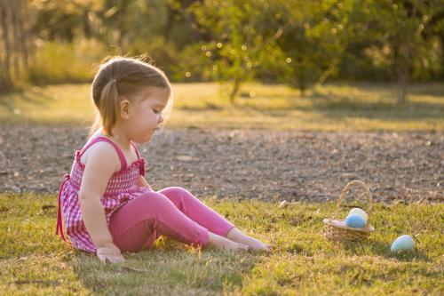 Little girl sitting on the grass near a basket of Easter eggs