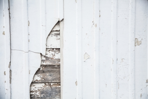 Close up of rustic timber slat panels hidden behind white wall