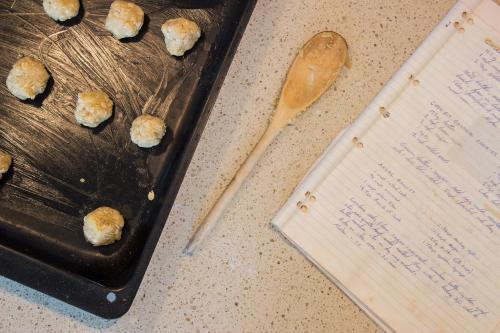 Uncooked ANZAC biscuits and handwritten recipe book