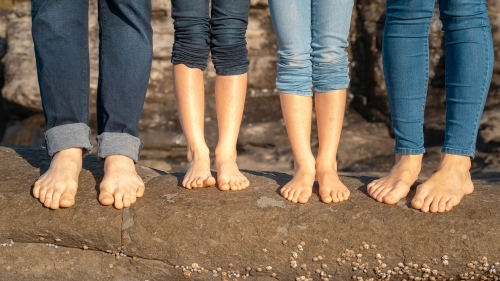 Close of family of four feet on the rocks at beach